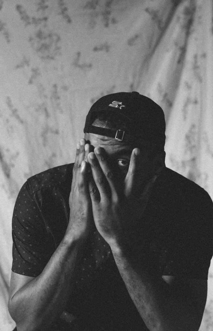 monochrome photo of a man hiding his face